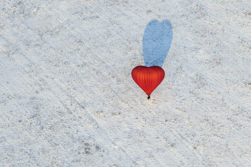 High angle view of heart shape hot air balloon flying over snowy land