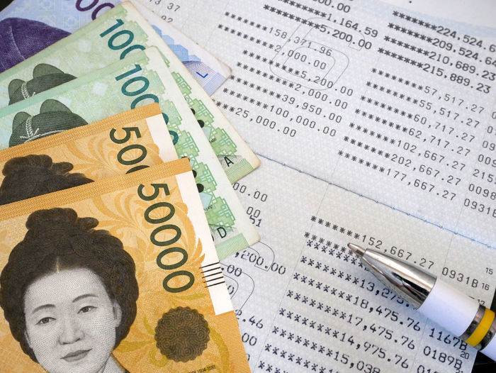 Korean won banknote and pen on bank statement, saving investment concept. Economy Korea Statement Account Bank Banknote Business Corporate Business Currency Debt Earnings Exchange Rate Finance Financial Home Finances Investment Making Money Money Number Paper Paper Currency Savings Trading Wealth Won