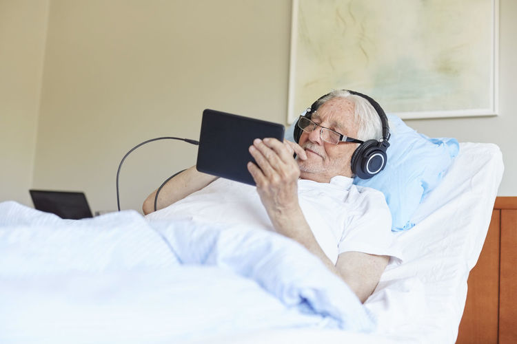 Midsection of man using mobile phone on bed