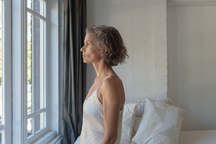 Woman at window One Person Indoors  Looking Window Contemplation Lifestyles Side View Real People Adult Standing Day Looking Away Domestic Room Leisure Activity Day Dreaming Women Home Interior Wall - Building Feature Profile View Hairstyle Beautiful Woman