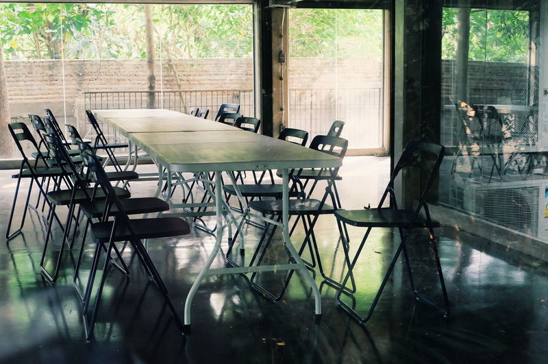 Empty chairs and tables in glass window