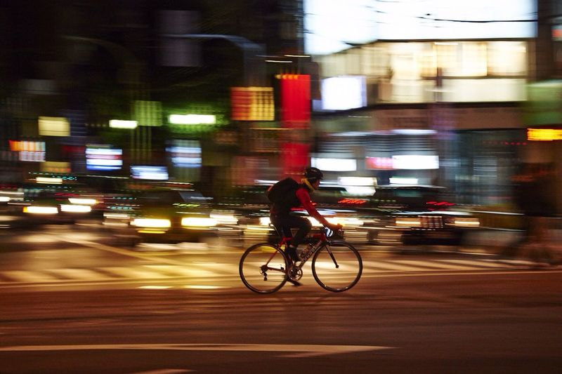 Side view of man bicycling on road against blurred cars
