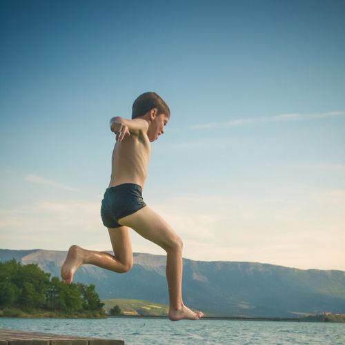 Full length of shirtless boy jumping in sea