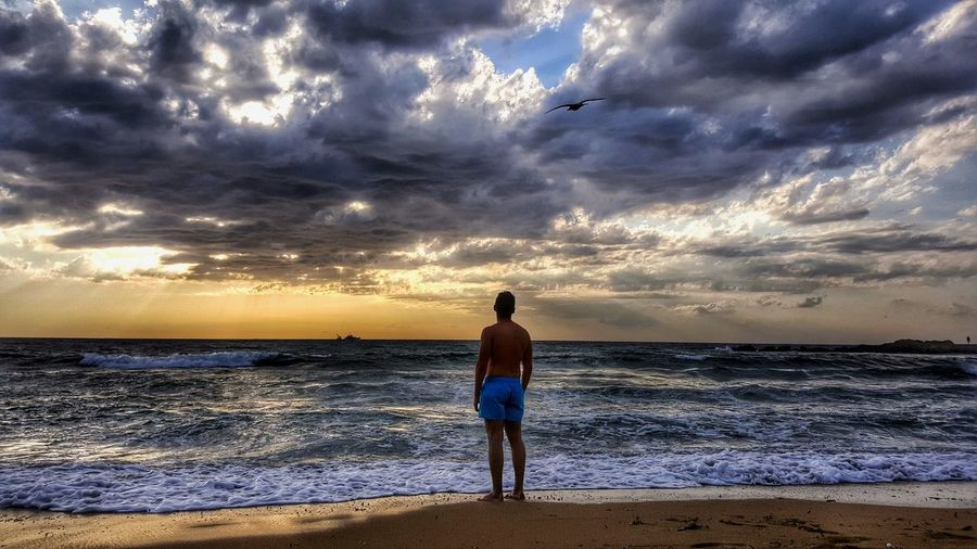 Rear View Of Man Standing At Beach Against Cloudy Sky During Sunset