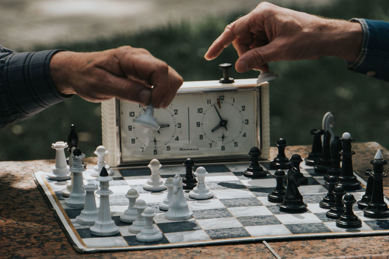 Midsection of man playing with chess against blurred background