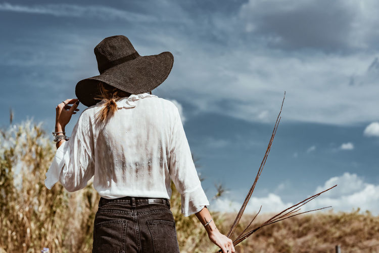 Hat Real People Women Leisure Activity Clothing Lifestyles Three Quarter Length Casual Clothing Focus On Foreground Sky One Person Nature Standing Land Adult Cloud - Sky Day Rear View Field Outdoors Hairstyle Looking At View