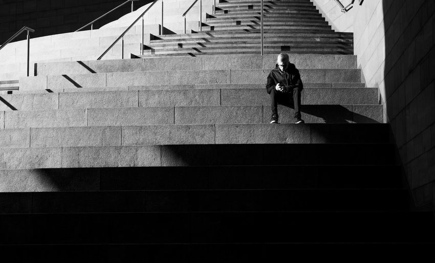 Steps in a shopping centre, Liverpool One, in brilliant winter sunshine Black And White Blackandwhite Lifestyles Mobile Phone Phone Shadow Sitting Staircase Steps Steps And Staircases Street Photography Streetphotography Sunlight Young Adult
