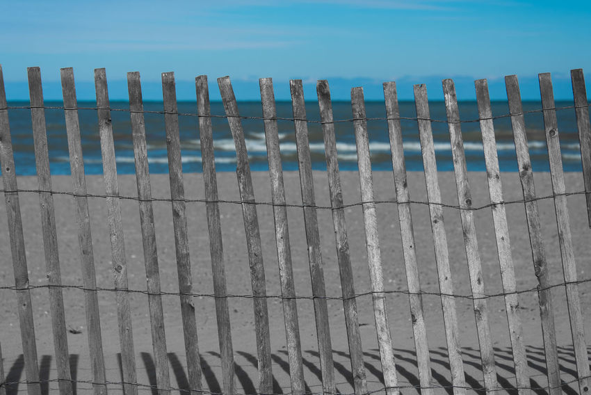 Barbed Wire Barricade Beach Close-up Day In A Row Nature No People Outdoors Protection Safety Sand Sea Separation Sky Wood - Material Wooden Post