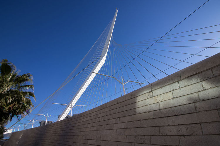 Low angle view of cables on building against clear blue sky