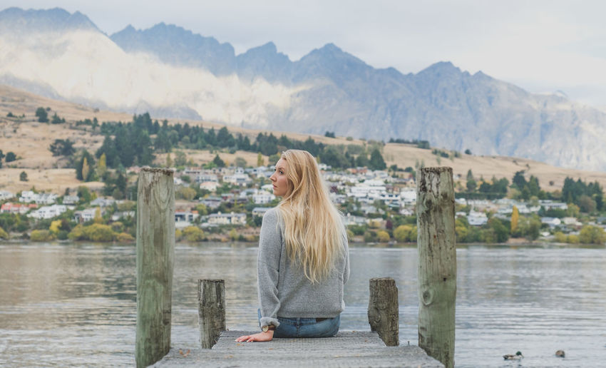 Architecture Beautiful Woman Beauty In Nature Blond Hair Built Structure Day Lake Leisure Activity Lifestyles Long Hair Mountain Mountain Range Nature One Person Outdoors People Real People Scenics Sitting Sky Water Women Young Adult Young Women