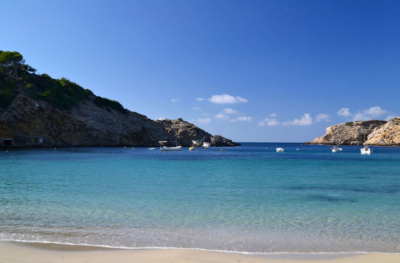 Landscape in Cala Vadella beach in Ibiza, Spain Balearic Islands Beach Blue Boat Cala Vadella Coastline Ibiza Idyllic Illes Balears Islas Baleares Mediterranean  Mountain Nature Nautical Vessel Outdoors Picturesque Scenics Sea Shore Tourism Tranquil Scene Travel Travel Destinations Vacations Water