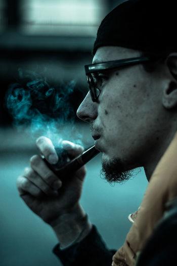 Cropped image of man smoking pipe