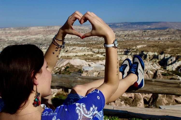 Rear View Of Woman Making Heart Shape With Hands While Relaxing By Railing