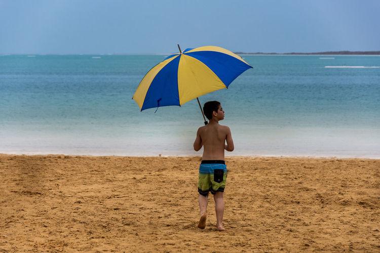 Rear view of boy walking on beach with umbrella