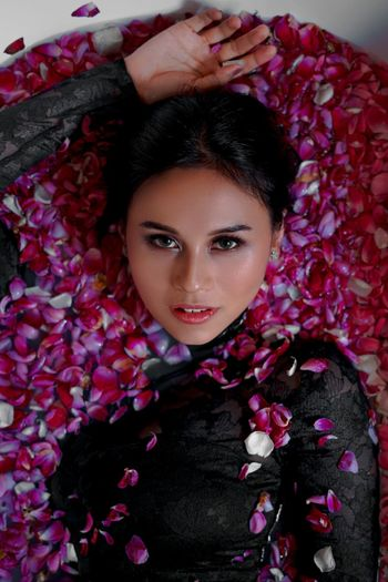 Portrait of woman with pink flower petals