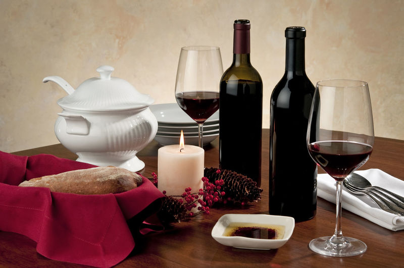 Wine and bread, table setting Drink Food And Drink Refreshment Wine Glass Bottle Alcohol Table Wineglass Indoors  Still Life Red Wine No People Food Drinking Glass Wine Bottle Olive Oil Silverware  Napkins Plates