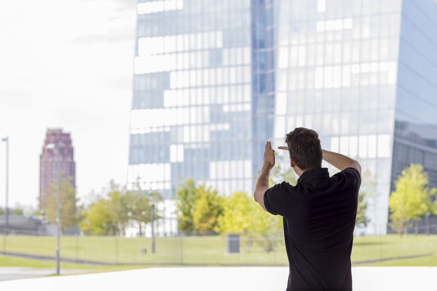 Casually dressed man, wearing ka golf shirt raising hands and pointing towards Frankfurt office buildings. Medium close up shot. Back turned away from camera. Architecture Bright Business City Grass Man Rear View Standing Sunny Trees Back Turned Buildings Casual Clothing Caucasian Day Gesturing Glass Hand Gesture Handsome Medium Shot Model Office Building Pointing Summer Urban