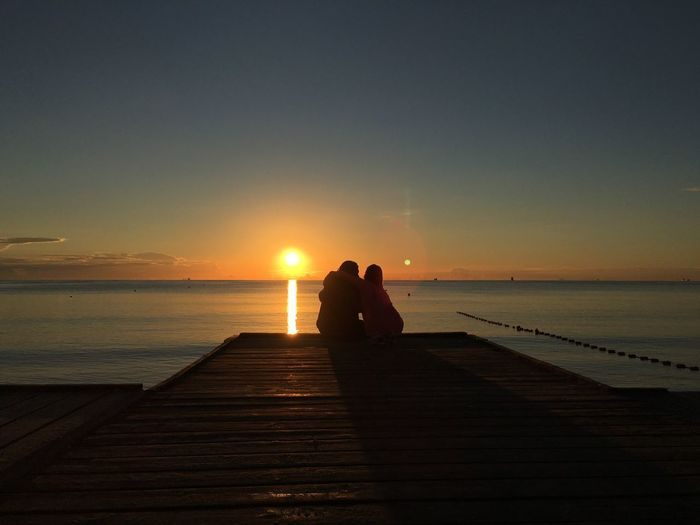 Silhouette couple sitting on sea against sky during sunset