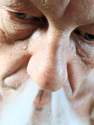 Close-up of man exhaling smoke