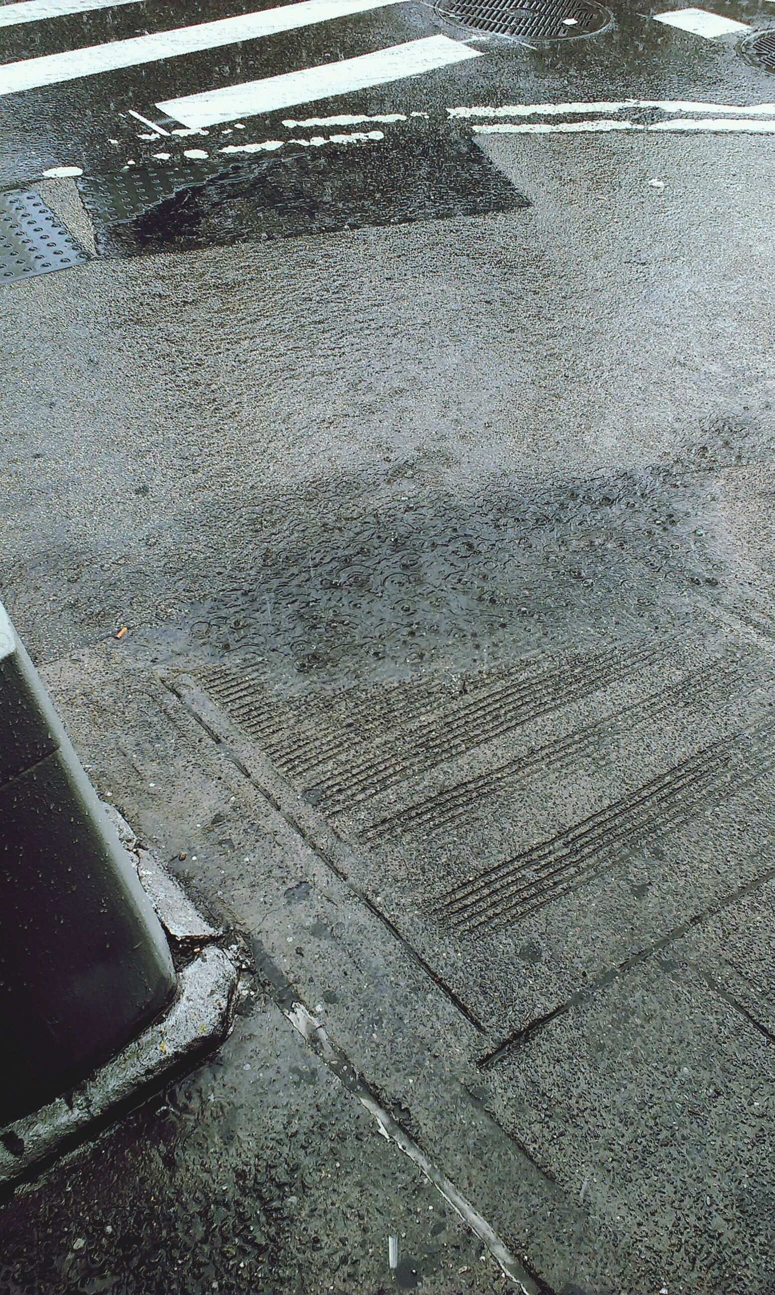 asphalt, street, road, high angle view, road marking, transportation, puddle, wet, day, outdoors, textured, no people, water, sunlight, full frame, sidewalk, rain, season, close-up, weather