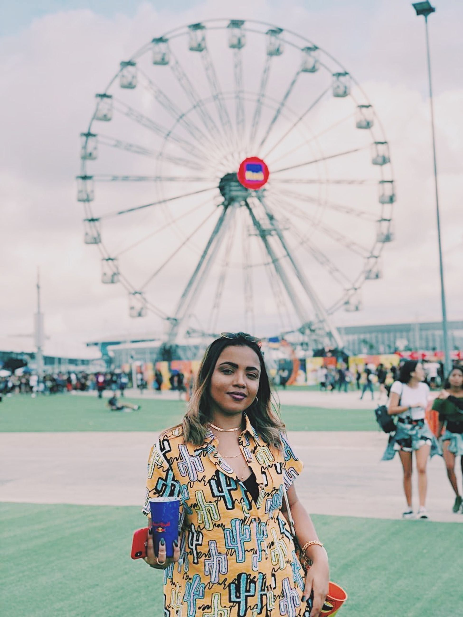 amusement park, amusement park ride, ferris wheel, leisure activity, real people, lifestyles, one person, women, focus on foreground, incidental people, arts culture and entertainment, young women, portrait, young adult, standing, front view, adult, casual clothing, architecture, hairstyle