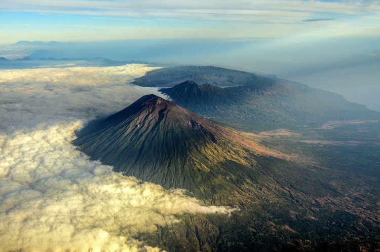 This is mount Agung. The highest volcano in Bali yet the most exotic one. The image was taken during early morning flight with Garuda Indonesia, departing from Denpasar to Makassar. Bali Bali, Indonesia Beautiful Nature Cloud Denpasar Garuda Indonesia Karangasem Lost In The Landscape Makassar Mount Agung Sulawesi Sulawesi Selatan Agung Airplane Window Airplane Window View Blanket Garuda Garudaindonesia Makassar-south Sulawesi-indonesia Makassarcity Ray Of Light Ray Of Sun, Rays Of Sunshine South Sulawesi Volcano