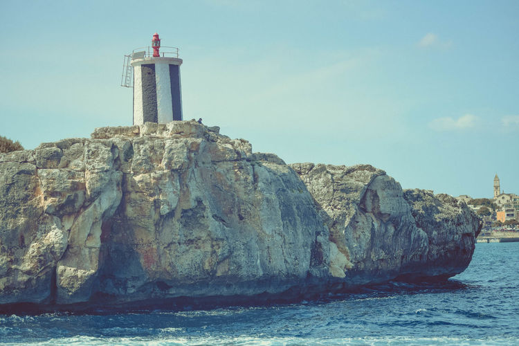 Lighthouse Tower Architecture Sky Built Structure Guidance Water Building Exterior Sea Rock Nature Rock - Object Building Waterfront Direction Solid No People Day Land Outdoors