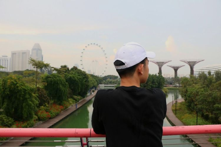 Rear view of man standing on bridge at gardens by the bay against sky