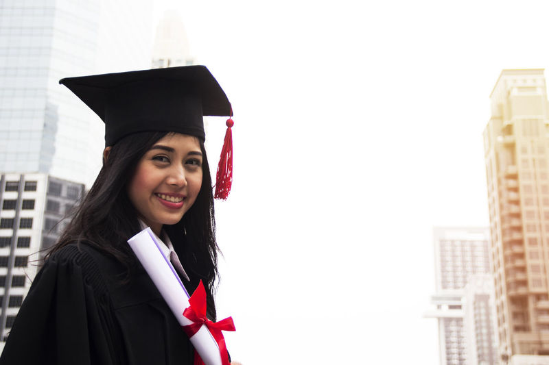 Portrait of smiling young woman in graduation gown