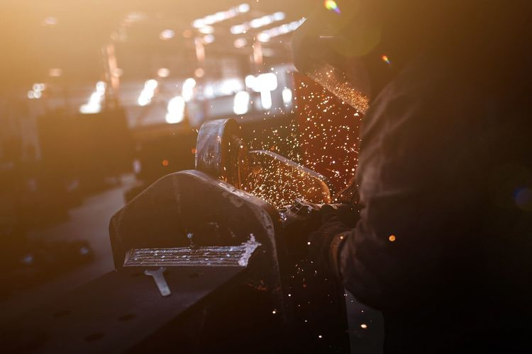 Midsection of person working on metal in workshop