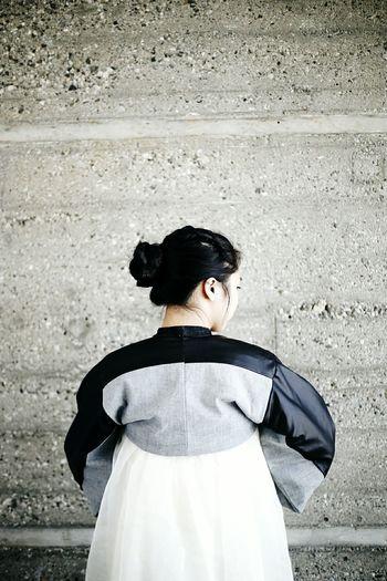 Young woman facing concrete wall