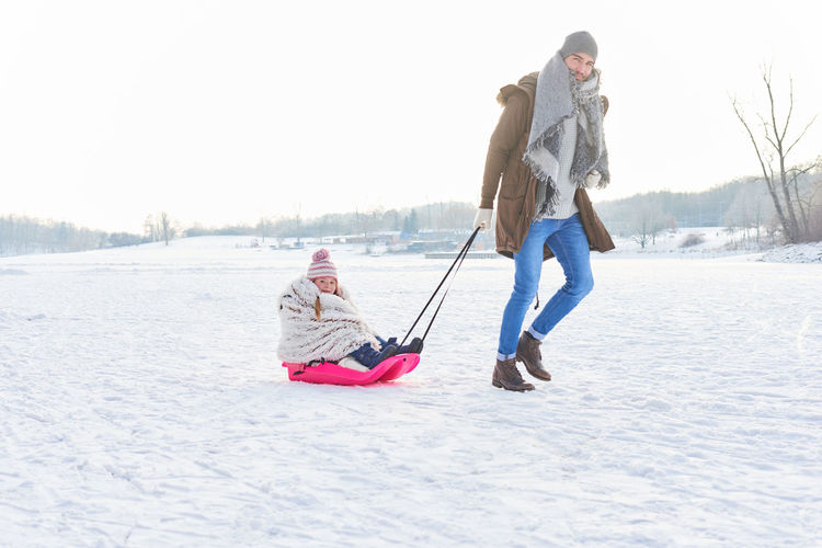 Father pulling his daughter on sledge during winter