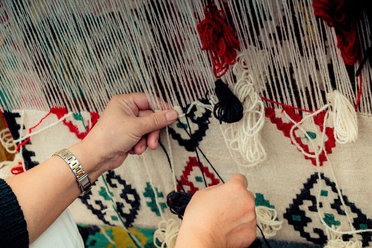 Cropped hand of woman working with wool indoors