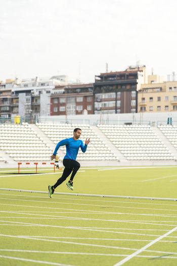 Side view of man running on grassland