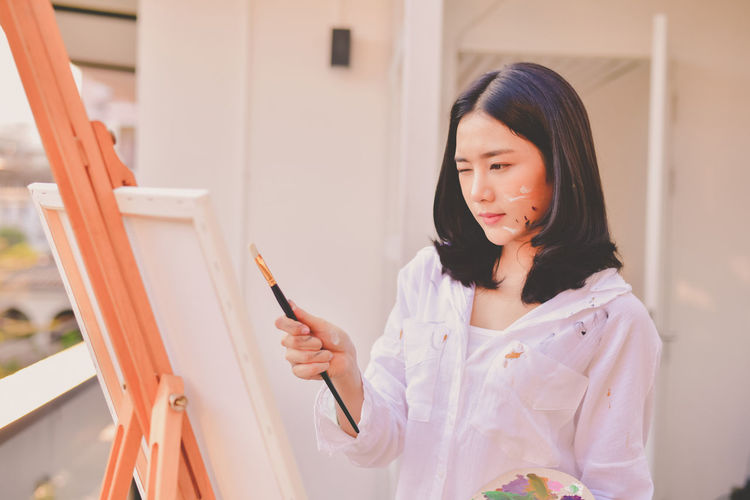 Black Hair Casual Clothing Easel Females Focus On Foreground Front View Hair Hairstyle Holding Leisure Activity Lifestyles Looking One Person Portrait Real People Standing Waist Up Women Young Adult Young Women