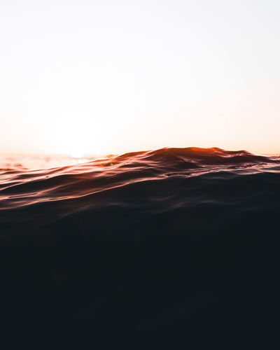 Scenic view of waves against clear sky during sunset