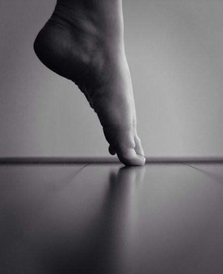 Low section of ballerina tiptoeing at dance studio