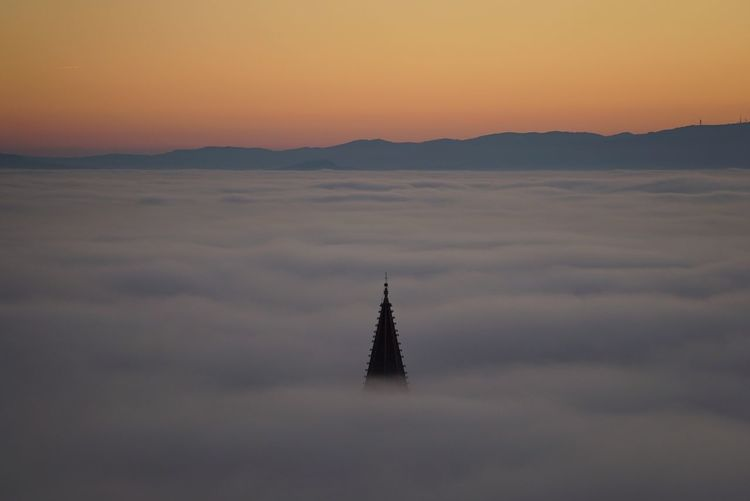 AERIAL VIEW OF CHURCH SPIRE IN FOG AT SUNSET