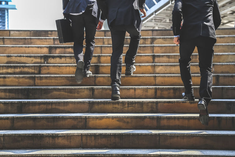 Low Section Of Businessmen Climbing On Steps