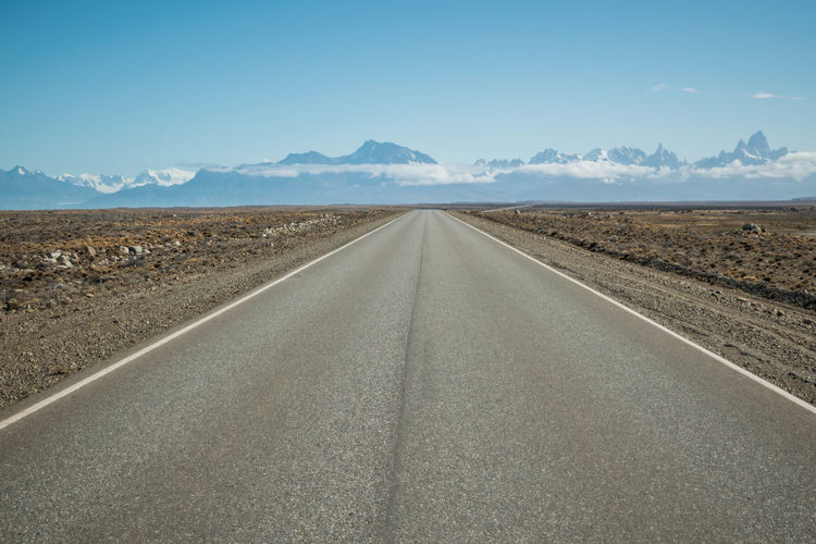 Road leading towards desert and snowcapped mountains against sky