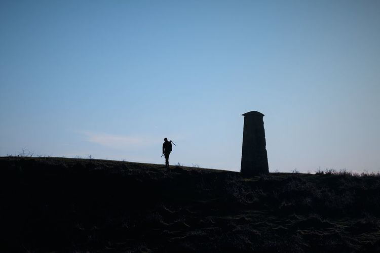 Silhouette photographer standing on a hill biside a tower against clear sky