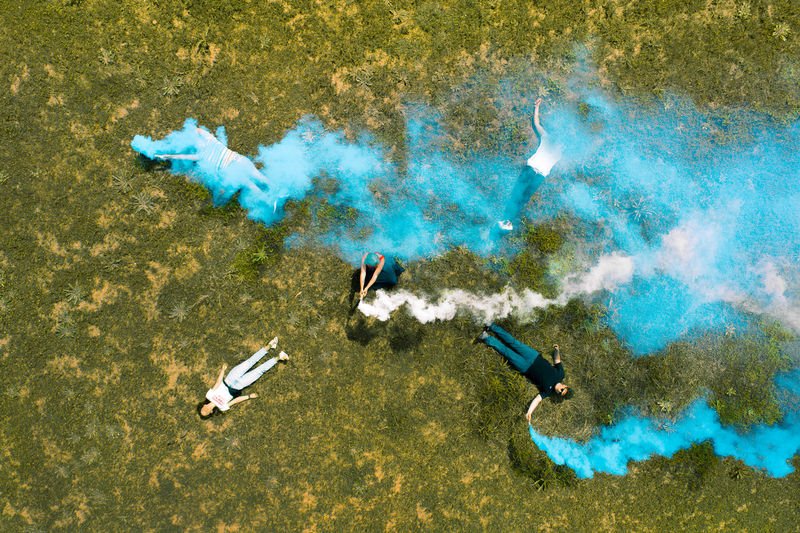 High angle view of people with smoke bombs lying down on field