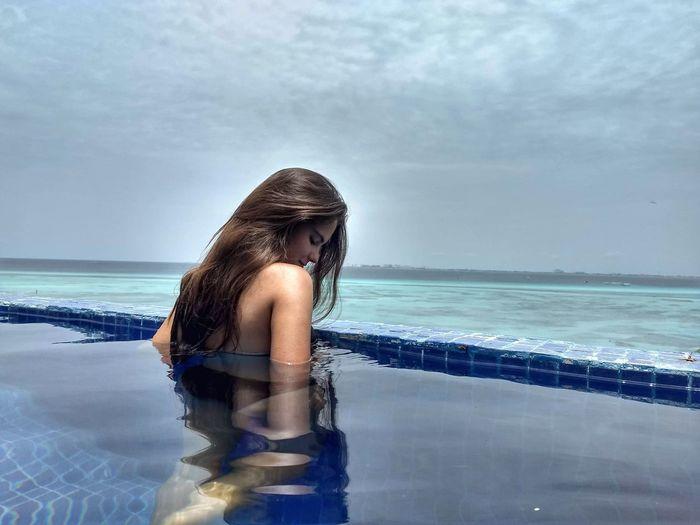 Teenage girl in infinity pool against sky