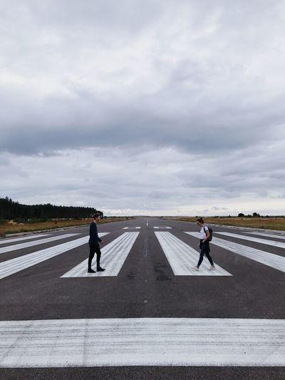 Friends walking on runway against cloudy sky