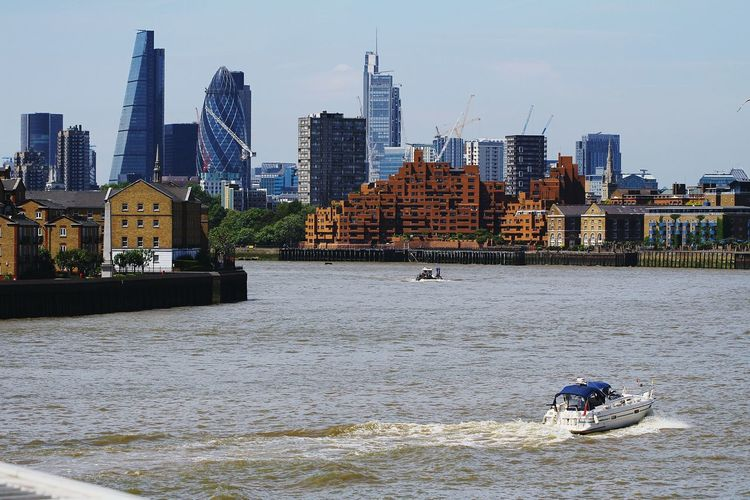Cityscape by thames river against sky