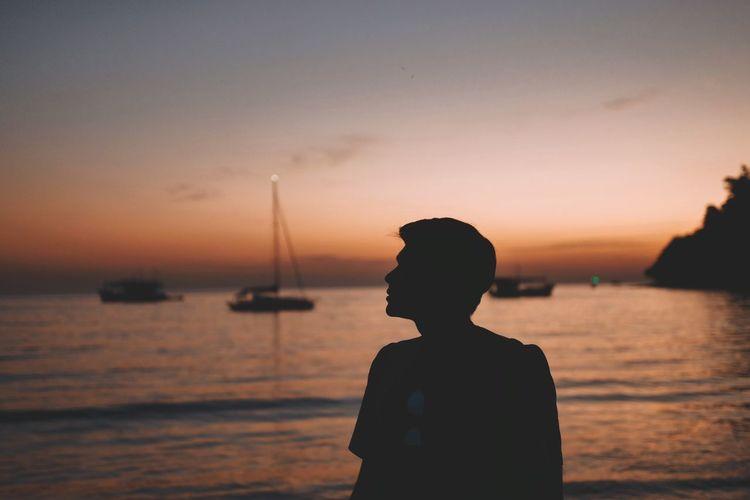 Silhouette man standing against sea at beach
