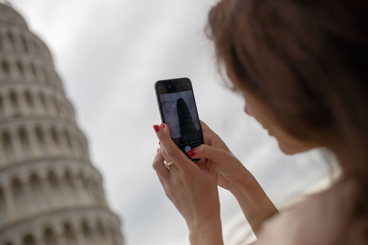 Woman taking picture of leaning tower of pisa