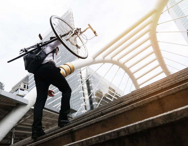 Business man riding bicycle go to worker. Architecture Bridge Bridge - Man Made Structure Building Exterior Built Structure Connection Day Full Length Lifestyles Low Angle View Men Metal Nature One Person Outdoors Railing Real People Sky Transportation
