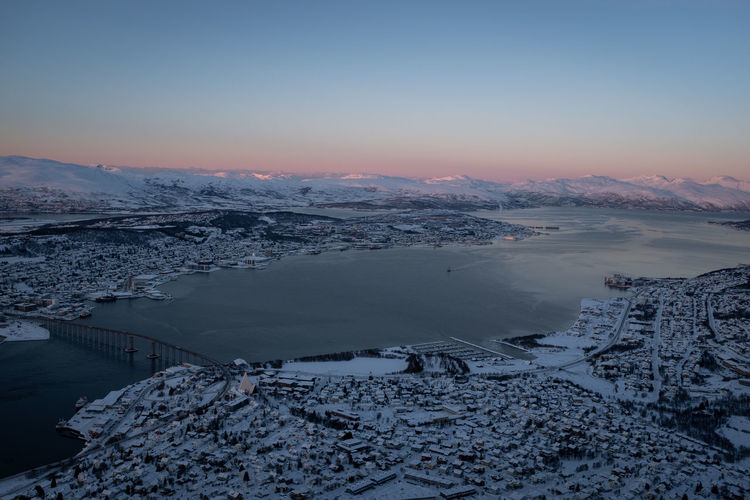 Tromsø norway cityscape in winter covered with snow. view of tromsøysundet strait. aerial shot.
