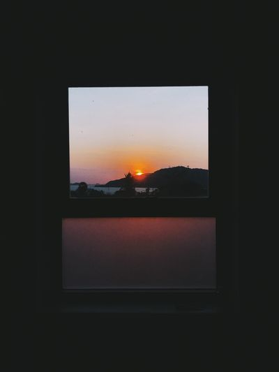 Silhouette buildings seen through window during sunset